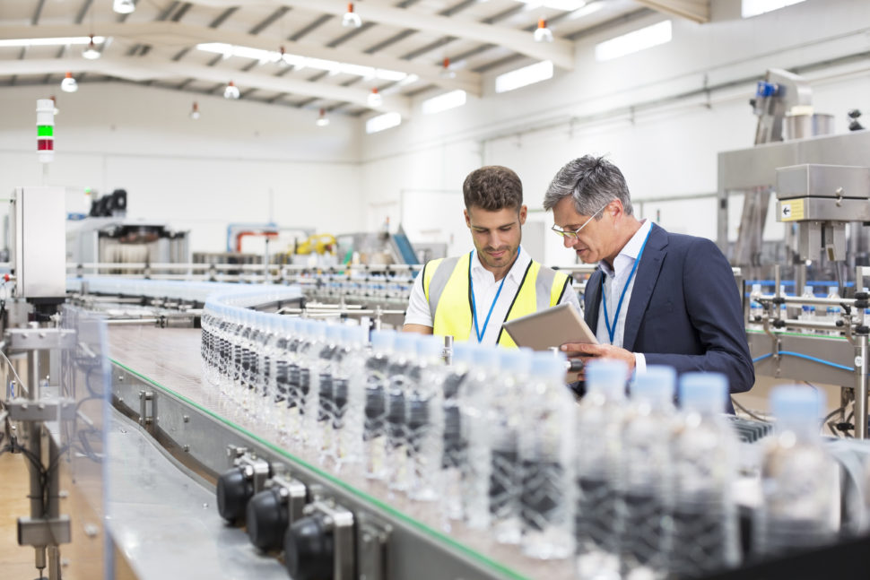 Supervisor and manager watching plastic bottles on conveyor belt